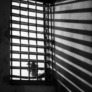 Cuban Girl Looking Out from Behind Bars