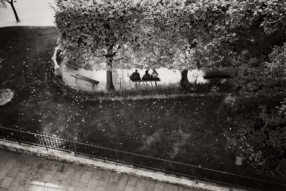 men on park bench from window-paris